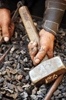 Detail of dirty hands holding hammer - blacksmith