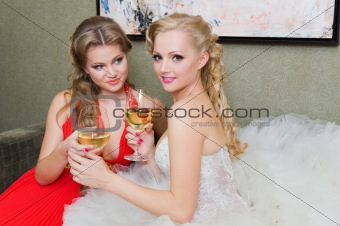 The bride and her bridesmaid with a glass of wine