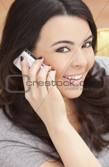 Happy Hispanic Woman Talking On Her Cell Phone At Home