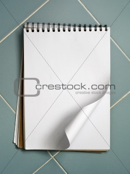 Blank white sketch book on blue