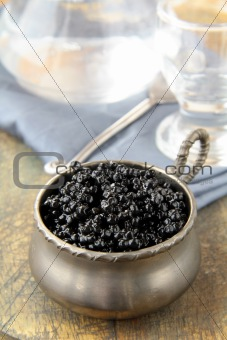 Black caviar in a glass jar on a white background
