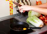 Woman cracking eggs into frying pan in kitchen