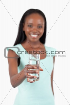Refreshing glass of water offered by young woman