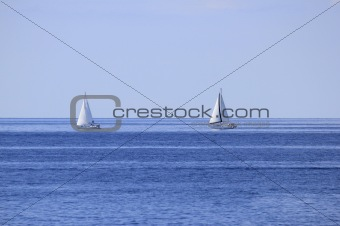 Two sailboats on open sea horizon