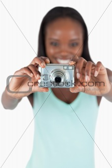 Camera used for taking photos by smiling young woman