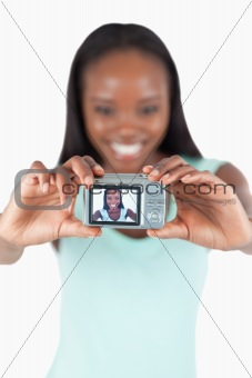 Smiling young woman taking picture of herself