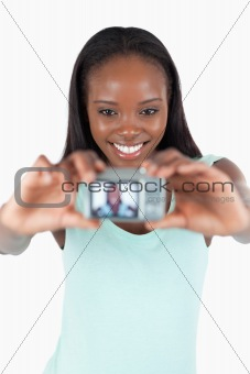 Smiling young woman taking photo of herself