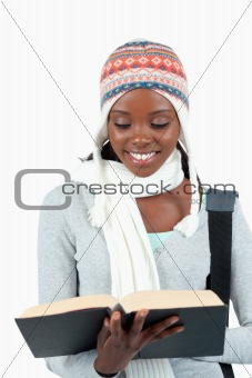Close up of smiling student in winter clothes reading in her book