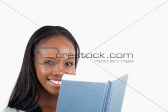 Side view of smiling woman reading a book