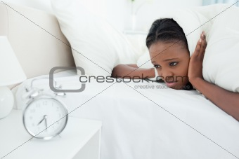 Tired woman being awakened by her alarm clock