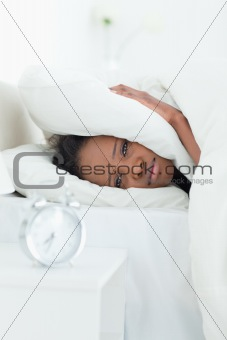 Portrait of a woman covering her ears while her alarm clock is ringing