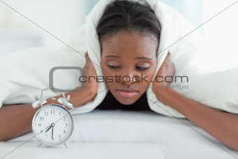 Tired woman covering her ears with a duvet