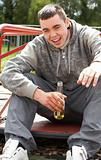 Young Man Sitting In Playground Drinking Beer