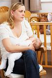 Worried Mother Breastfeeding Baby In Nursery