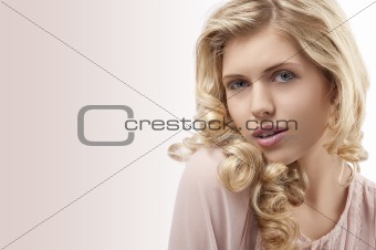 blond young girl with curly hair and beautiful face looking at t