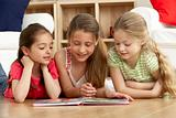 Three Young Girls Reading Book at Home