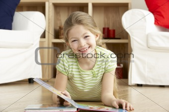 Young Girl Reading Book at Home