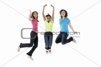 Group of Teenage Girlfriends Jumping in Studio