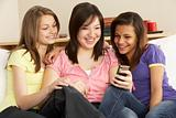 Teenage Girlfriends Reading Mobile Phone at Home