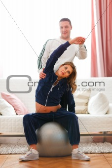 Husband helping his beautiful pregnant wife making sport exercise on fitness ball