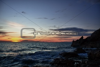 Sunset, rocks and fisherman on sea