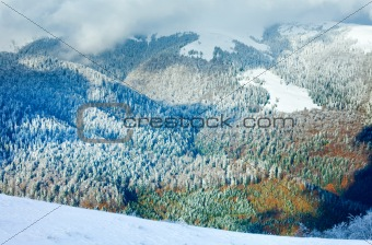 First winter snow and last autumn colorful foliage in mount