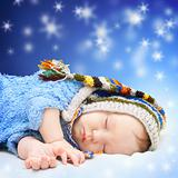 Baby sleeping in cute hat. Magic night sky background.