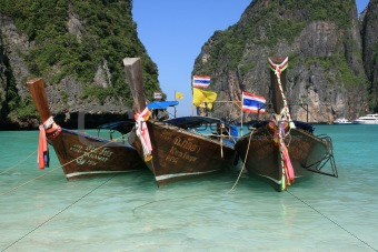 Longtail boats in purple water at Maya Bay