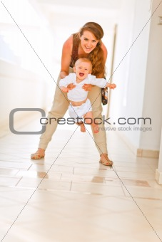 Smiling mother playing with her adorable baby