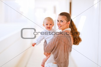 Portrait of young mama with adorable baby in hand