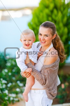 Portrait of beautiful mother with cute little baby on street