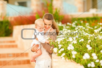 Caring mother showing plants to her interested baby