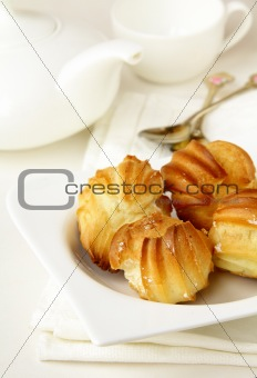 cake profiteroles on a plate, white background