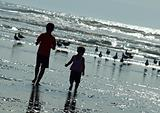 Two Kids Playing on the Beach as the Sun is Glistening on the Water