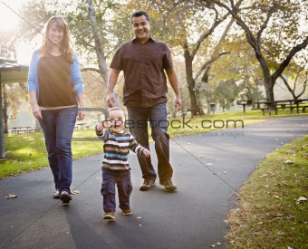 Happy Young Mixed Race Ethnic Family Walking In The Park.