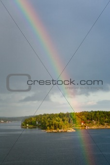 rainbow in rain during sunshine in Baltic sea