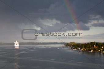 white cruise liner and rainbow