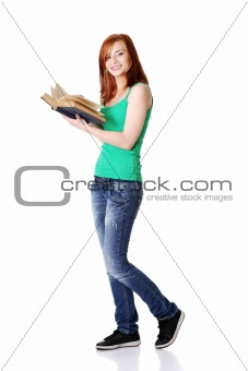 Smiling teen student holding a book.