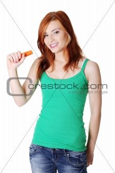 Teen standing girl holding a carrot.