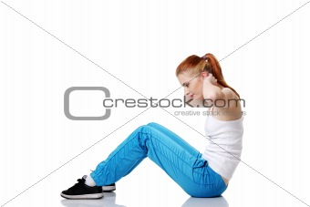Teen student doing exercises on the floor.