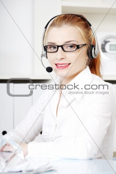 Caucasian woman in headset sitting behind the desk.