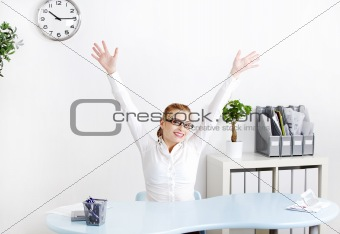 Young woman in the office with hands in the air.