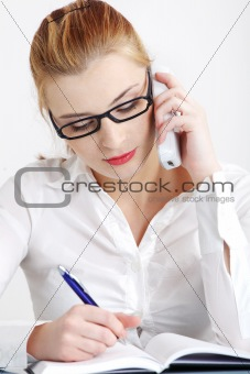 Businesswoman answering the phone and writing.