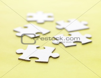 Jigsaw puzzle pieces on yellow background