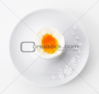 Lightly boiled egg in cup with salt on white background