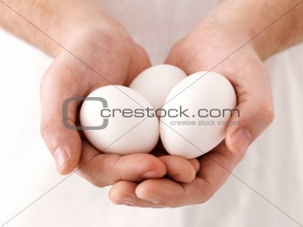 Three white eggs in human hand