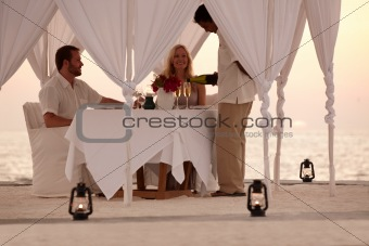 Honeymoon couple enjoying romantic dinner by the sea