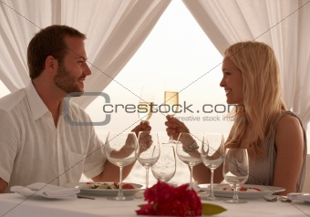 Young couple on a romatic date toasting wine