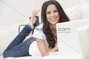 Young Brunette Woman Using Laptop Computer At Home on Sofa