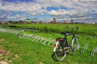 Bicycle on the green lawn against the backdrop of windmills.
